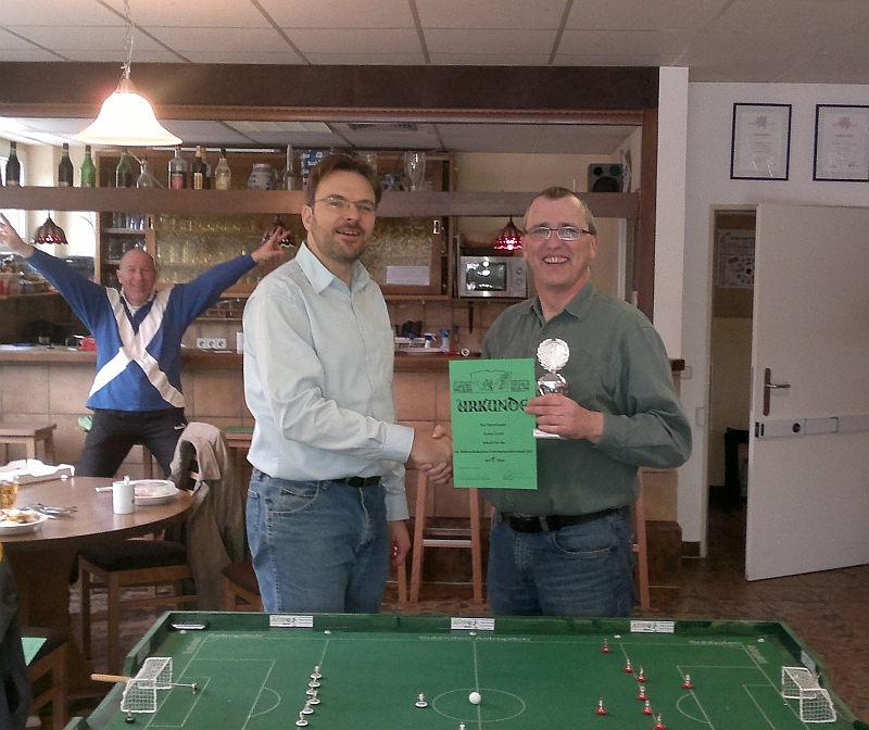 Siegerehrung: Janus Gersie (rechts) erhält von         Spielleiter Stephan Thiele den Pokal. Michael Kappl (hinten)         freut sich.